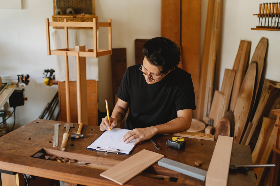 Concentrated man in glasses sitting at wooden table in workshop and holding pencil while creating new object on paper