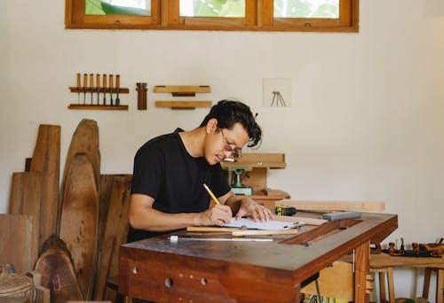 Focused ethnic man working in joinery workshop