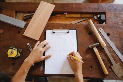 Crop artisan sketching on paper in workshop