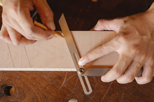 Top view of crop anonymous woodworker drawing diagonal line on wooden block using bevel on workbench