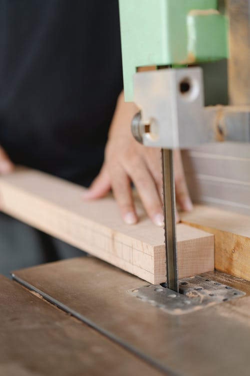 Crop woodworker cutting wooden plank with band saw