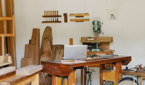Workshop interior with wooden planks and laptop on workbench