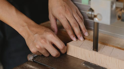 Crop carpenter cutting wooden block with band saw