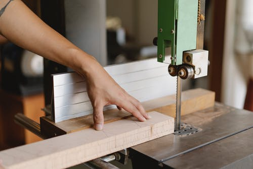 Faceless woodworker sawing lumber with band saw