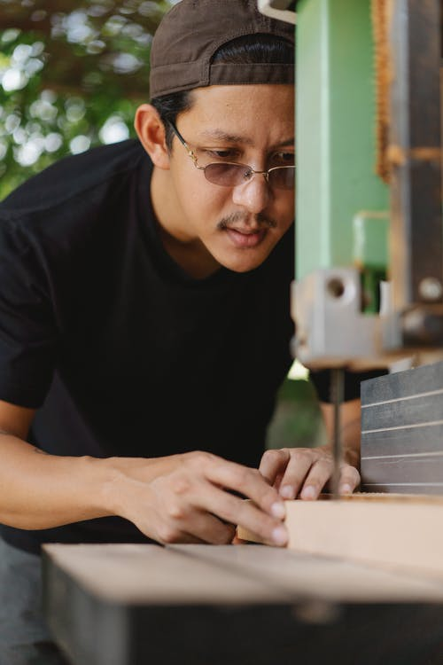 Crop focused young ethnic male woodworker in eyeglasses cutting wooden plank using electric equipment in garden
