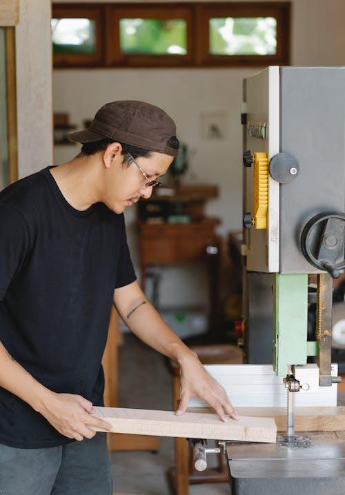 Focused Asian artisan preparing to saw timber near workshop