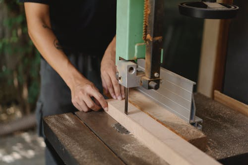 Faceless carpenter cutting timber with band saw on table