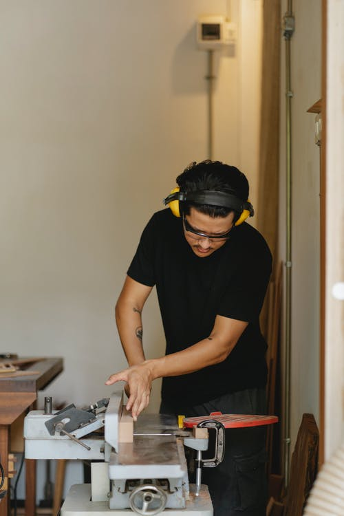 Concentrated Asian carpenter leveling lumber on jointer in workshop