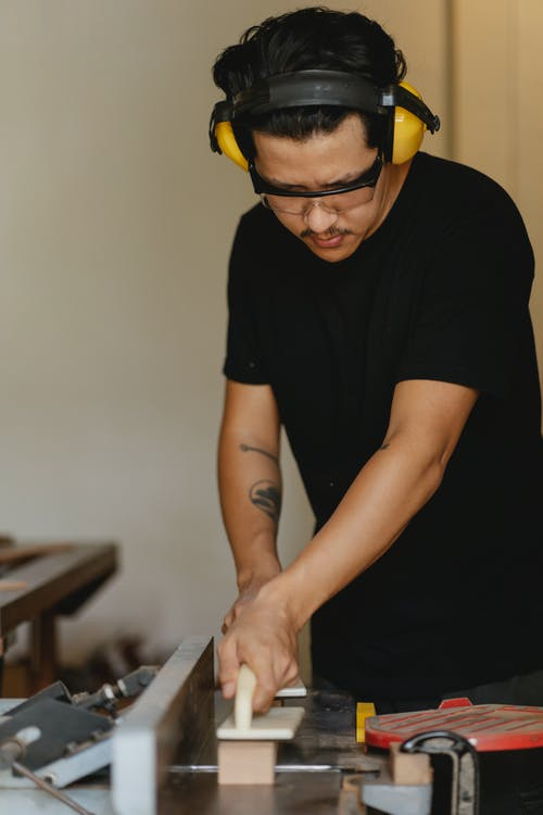 Focused Asian joiner leveling timber on jointer in workroom