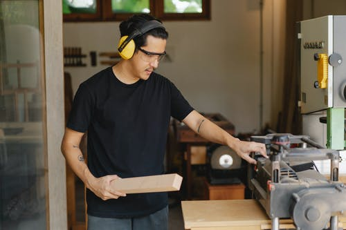 Asian carpenter with lumber near planer and workshop