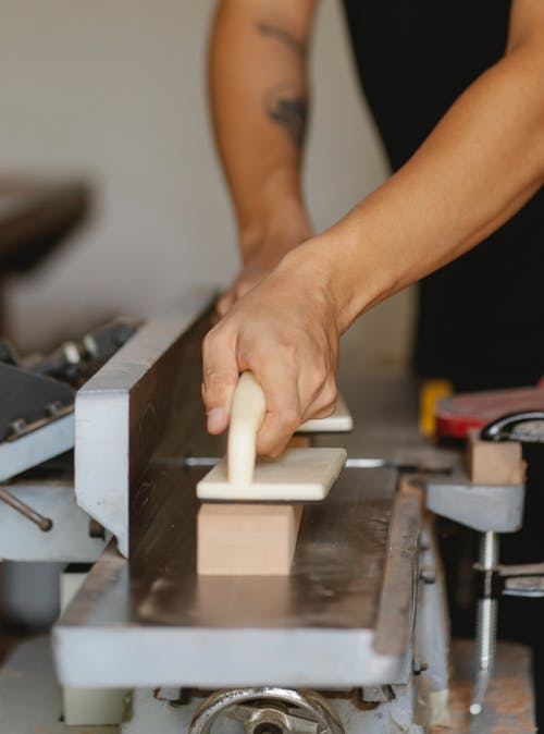 Faceless artisan leveling lumber on jointer in workroom