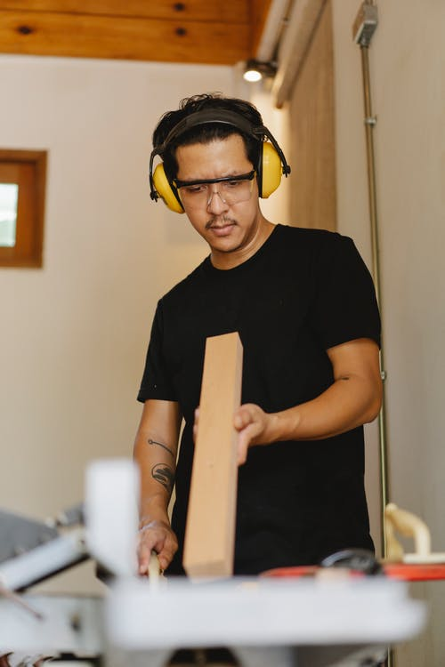 Serious Asian woodworker with timber near jointer in workroom