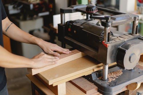 Crop artisan flattening lumber on planer in workroom