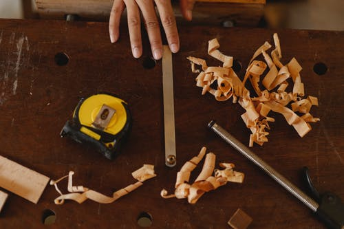 From above of crop anonymous woodworker with assorted instruments and wooden shavings in workshop