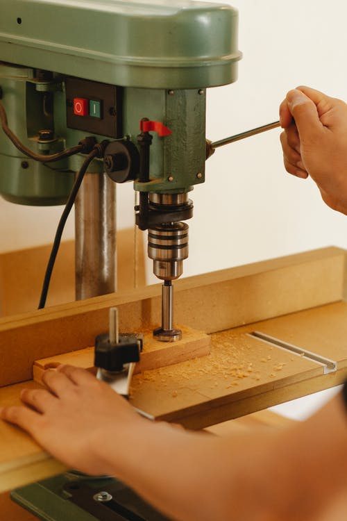 Faceless artisan drilling wooden block with drill press in workshop