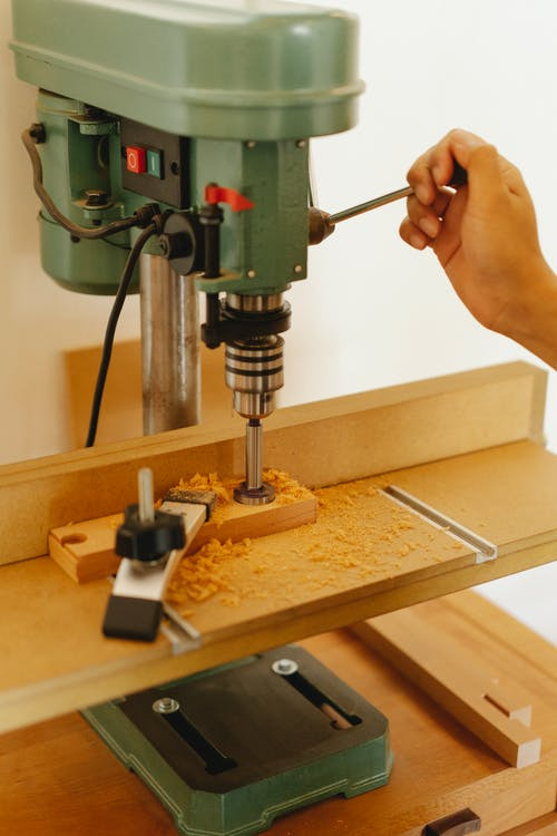 Crop woodworker drilling timber with drill press in workroom