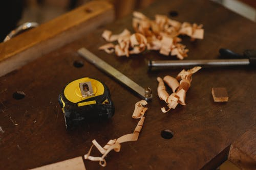 Assorted artisan tools with wooden shavings on workbench