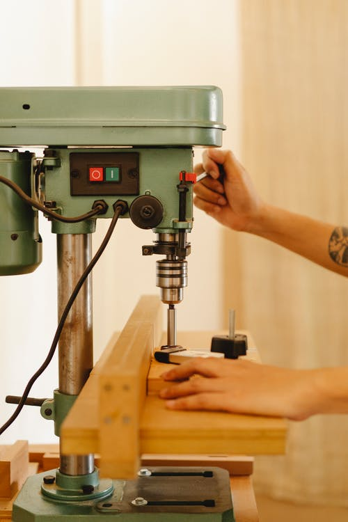 Faceless artisan working with drill press in workroom