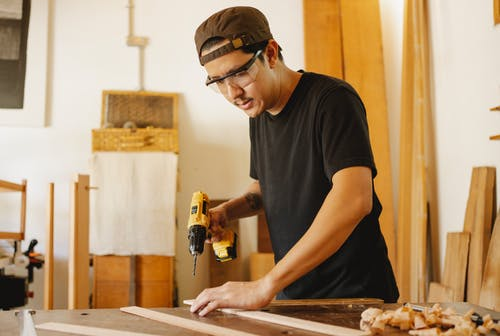 Asian joiner with drill and lumber in workshop