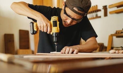 Crop man working with drill in workshop