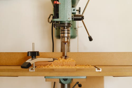 Professional drill machine for cutting wooden details near white wall in modern workshop