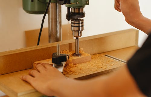 Crop anonymous carpenter using drill press to cut wooden detail while creating new furniture in workshop