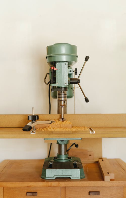 Contemporary drill press for woodwork on timber cabinet near white wall in workroom