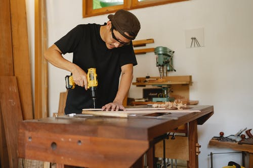 Focused man in cap standing near workbench and drilling hole in plank while repairing wooden detail