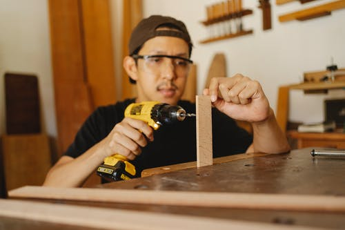 Focused Asian male in cap and glasses holding drill and wooden detail while working in modern workshop