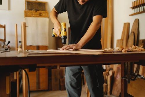 Crop carpenter drilling wooden plank in workshop