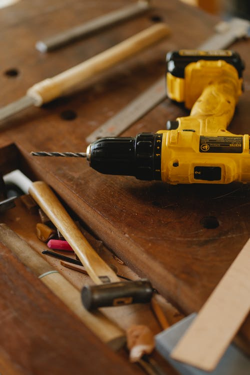 From above of contemporary screwdriver with drill near hammer and tools on wooden desk