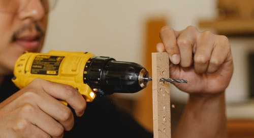 Crop man drilling holes in wooden plank
