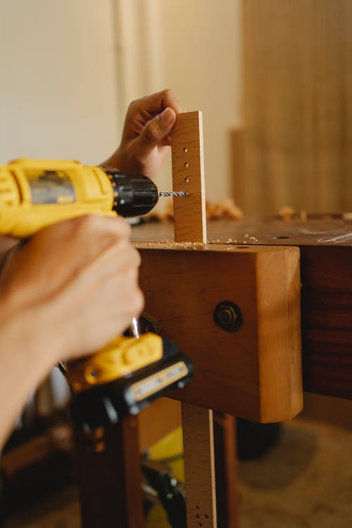 Crop anonymous skillful male using screwdriver while drilling holes in timber detail in workshop