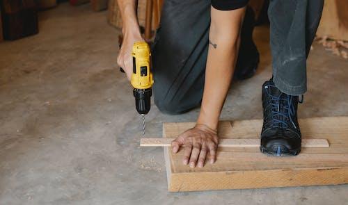 Man drilling wooden plank in workshop
