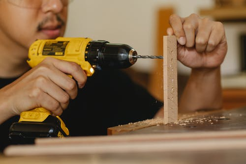 Crop anonymous male drilling holes in wooden panel while working on table in workshop