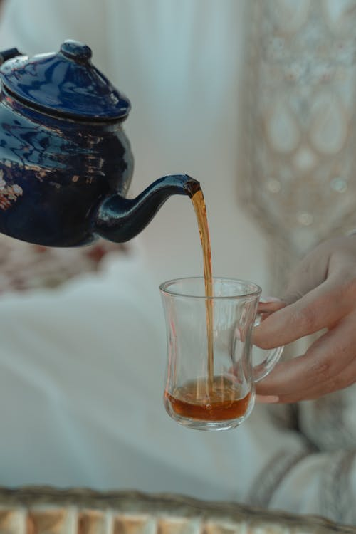 Person Holding Blue Ceramic Teapot Pouring Tea on Clear Drinking Glass
