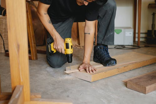 Man drilling piece of wooden with screwdriver