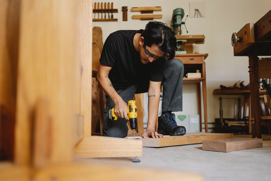 Pensive male drilling wooden surface of plank in workshop with equipment for carpentry