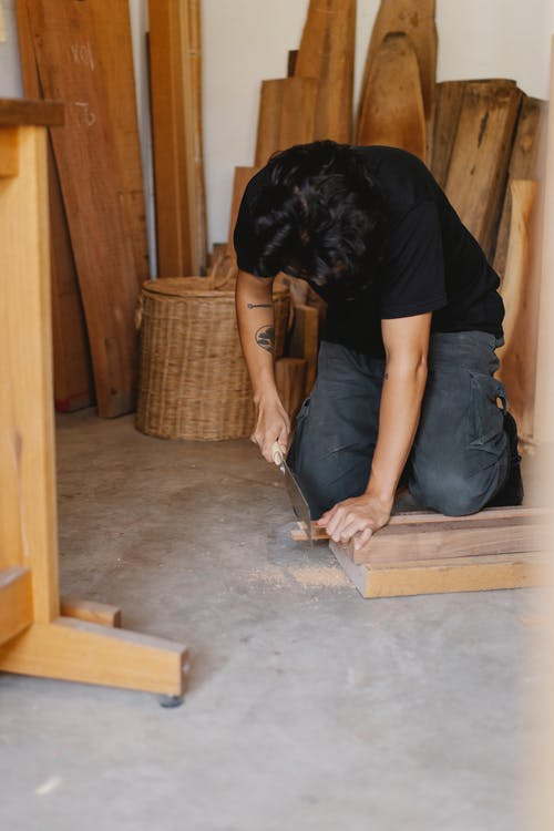 Focused joiner sawing piece of wood plank in workshop