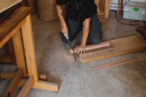 Anonymous joiner working with Japanese saw while cutting edge of timber plank on floor in workshop