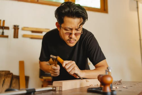 Focused ethnic artisan cutting joint with chisel