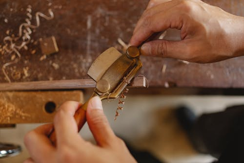 High angle of crop carpenter carving wooden detail with router plane while working at workbench in joinery workshop