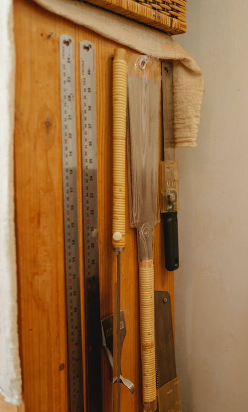 Set of various instruments for carpentry including rulers hanging with saws on wooden wall in joinery workshop