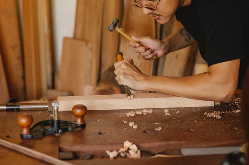 Focused artisan making hole on plank with hammer and chisel