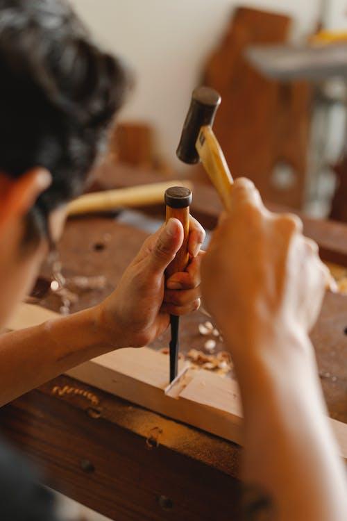 Craftsman hammering chisel into wooden plank