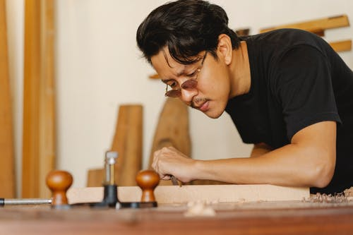 Concentrated precise Asian craftsman in eyeglasses creating wooden detail with chisel while working in joinery