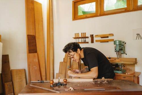 Side view of concentrated Asian craftsman creating wooden plank with hammer and chisel during work in professional joinery