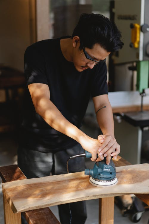 Concentrated male woodworker in protective goggles standing in carpentry workshop and polishing wooden object with sander