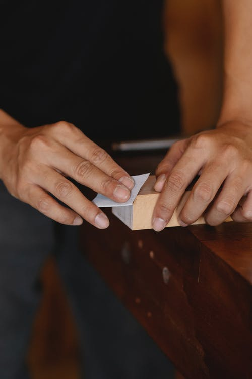 Crop anonymous craftsman sanding wooden board with piece of sandpaper while working in carpentry workshop