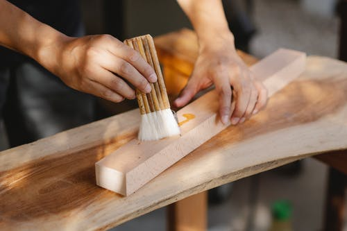 Craftsman smearing wooden plank with oil